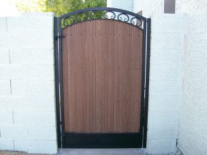 Decorative wrought iron and composite wood gate secures a home's yard.