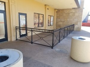 Black wrought iron fencing encloses restaurant patio