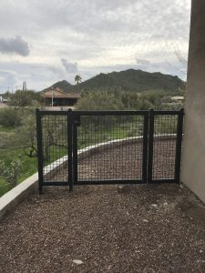 Black wrought iron gate secures a home's side yard.
