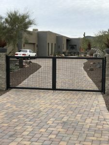 Black wrought iron gate secures a home's driveway.
