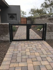 Black wrought iron gate secures a home's front courtyard.