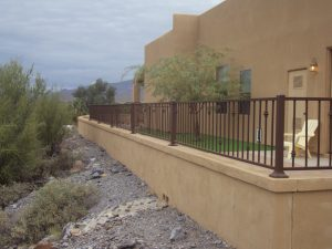 Wrought iron view fencing sits atop a home's stucco wall.