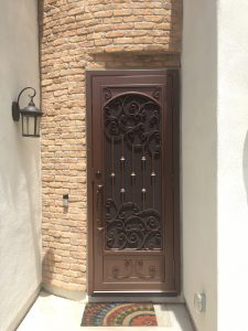 A bronze-colored wrought iron decorative security door provides a beautiful entrance to a home.