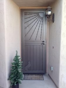 A wrought iron decorative security door features Southwestern imagery, including rays of sunshine and a howling coyote.