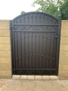 A solid, custom wrought iron gate with a decorative pattern secures the entrance to a home's yard.