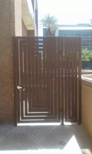 A contemporary-style wrought iron gate encloses a dumpster.