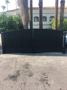 A custom wrought iron dumpster gate secures the trash enclosure on a commercial property.