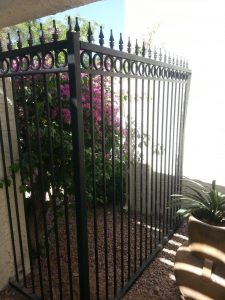 A galvanized wrought iron fence provides security for a commercial property.