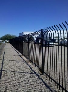 A black wrought iron fence secures a commercial property.