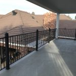 Black wrought iron railing secures a home's second-floor patio