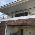 Black wrought iron railing secures a home's second-floor balcony
